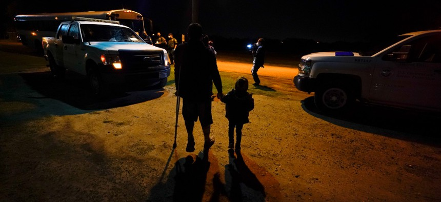 Pedro Mercado, 27, of El Salvador walks with one of his two daughters at an intake area after turning themselves in upon crossing the U.S.-Mexico border Wednesday, May 12, 2021, in La Joya, Texas.