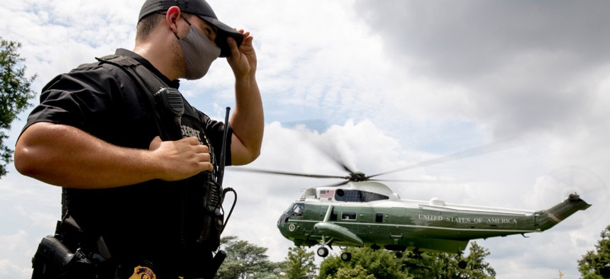 A member of the Secret Service stands guard as Marine One with President Donald Trump aboard takes off from the South Lawn of the White House in August 2020.
