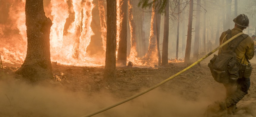 An Elk Mountain Hotshot using a hose on a 2018 California fire.
