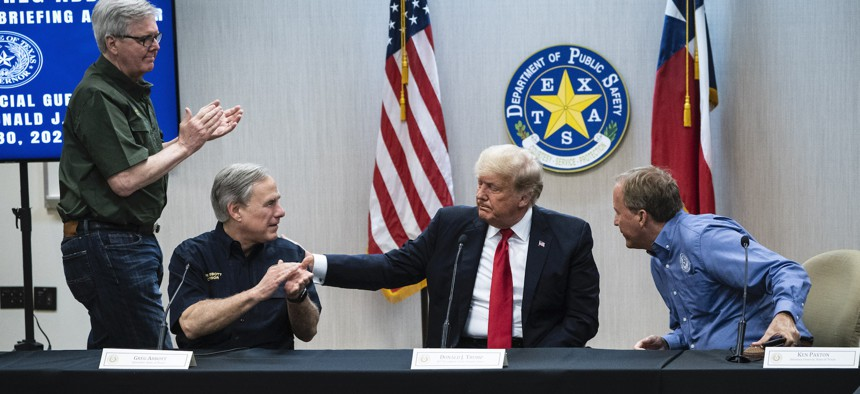 Former President Donald J. Trump and Texas Governor Greg Abbott, flanked by Texas Lt. Gov. Dan Patrick and Texas Attorney General Ken Paxton, attend a security briefing with state officials and law enforcement at the Weslaco Department of Public Safety DPS Headquarters before touring the border wall on Wednesday.
