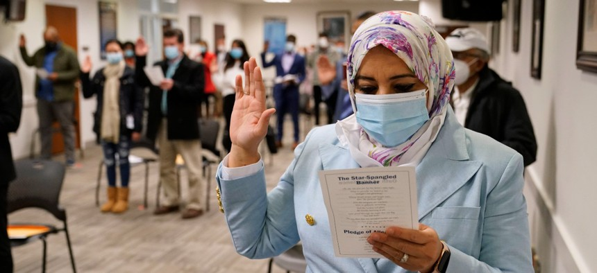 Candidates for American citizenship recite the Oath of Allegiance during a naturalization ceremony, Friday, Dec. 11, 2020, at the U.S. Citizenship and Immigration Services' Washington Field Office in Fairfax, Va.