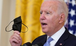 President Biden holds up a mask July 29 as he announces that millions of federal workers must show proof they've received a coronavirus vaccine or submit to regular testing and stringent social distancing, masking and travel restrictions.