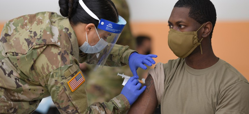 U.S. Army Spc. Eyza Carrasco, left, with 2nd Cavalry Regiment, administers a COVID-19 vaccination at the 7th Army Training Command's Rose Barracks, Vilseck, Germany, May 3, 2021.