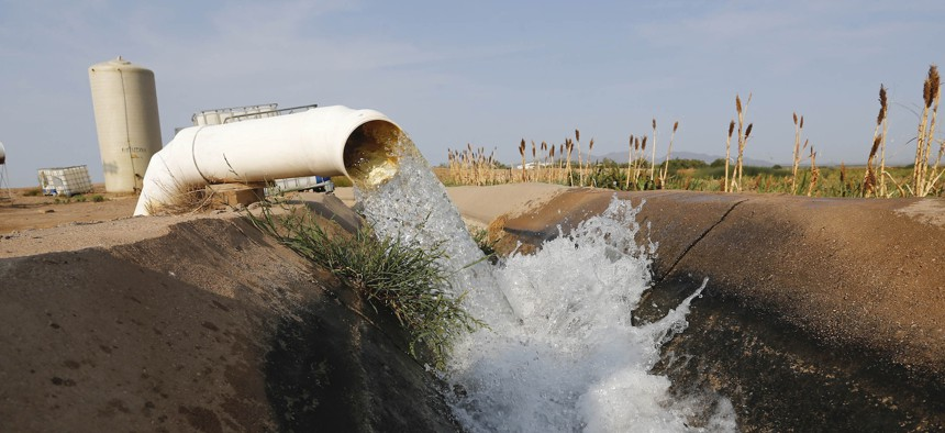 Water flows into a canal that feeds farms in Casa Grande, Ariz