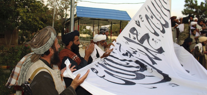 Taliban fighters pray while raising their flag at the Ghazni provincial governor's house, in Ghazni on Aug. 15.