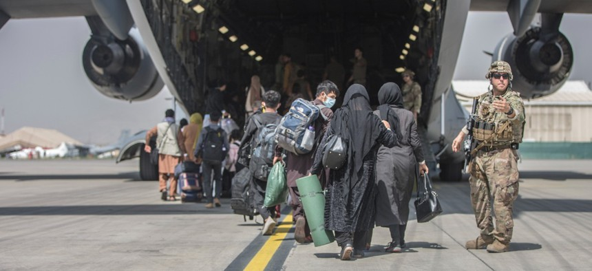 Families begin to board a U.S. Air Force Boeing C-17 Globemaster III during an evacuation at Hamid Karzai International Airport in Kabul, Afghanistan, on Monday.