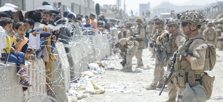 U.S. Marines with Special Purpose Marine Air-Ground Task Force - Crisis Response - Central Command, provide assistance during an evacuation at Hamid Karzai International Airport, Kabul, Afghanistan, Aug. 20.