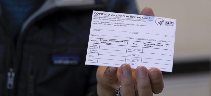 A nurse displays a real COVID-19 vaccination card.