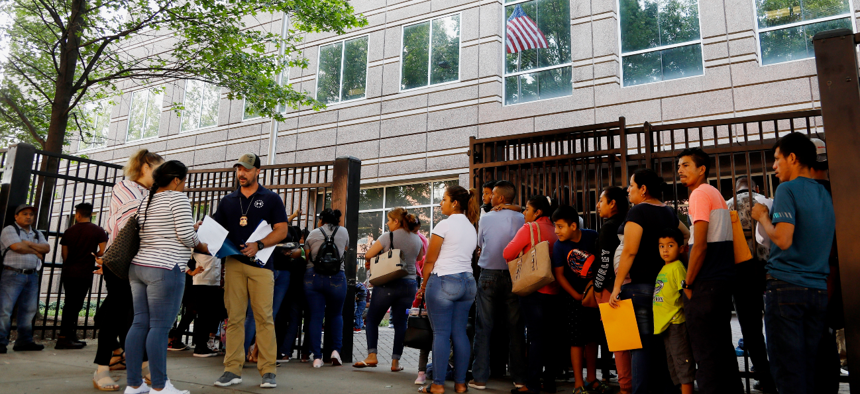 In this 2019 photo, an Immigration and Customs Enforcement official assists people waiting to enter the building that houses ICE and the immigratioIn this June 12, 2019, photo, an Immigration and Customs Enforcement official assists people waiting to enter the building that houses ICE and the immigration court in Atlanta.
