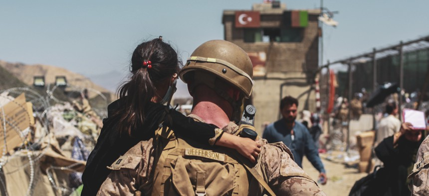 A Marine assigned to Special Purpose Marine Air Ground Task Force-Crisis Response- Central Command carries a child to be processed during an evacuation at Hamid Karzai International Airport, Kabul, Afghanistan, Aug. 25.