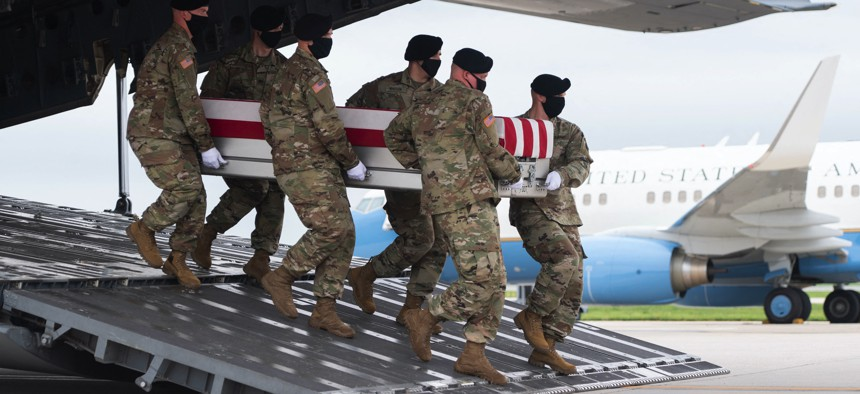 A transfer case with the remains of Army Staff Sgt. Ryan C. Knauss, 23, of Corryton, Tennessee, are carried off of a military aircraft at Dover Air Force Base in Dover, Delaware, August, 29, 2021