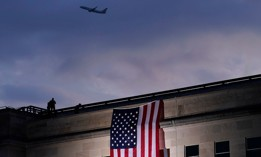 A plane takes off from Washington Reagan National Airport on Sept. 11, 2020, as a large American flag is unfurled at the Pentagon ahead of ceremonies at the National 9/11 Pentagon Memorial to honor the people killed in the 2001 terrorist attack.
