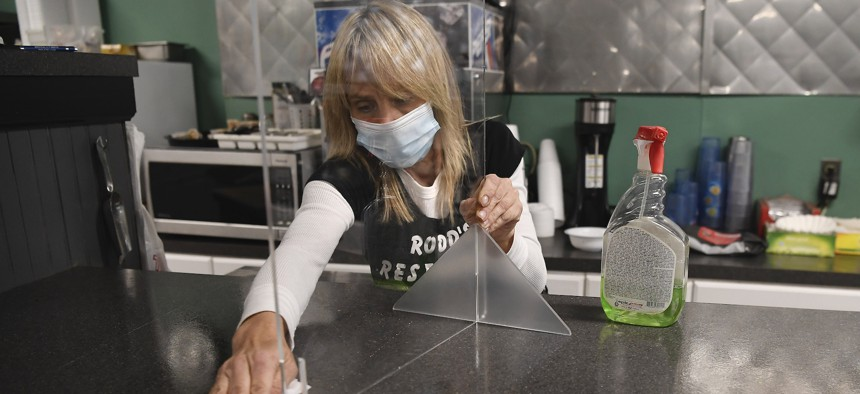 Head waitstaff Laurie Mitchell sanitizes a countertop at Rodd's Restaurant in Bristol, Connecticut, in December. New England states are the slowest to recover jobs during hiring problems for workplaces that require public contact amid the pandemic's delta variant surge.