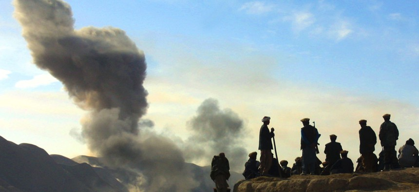Northern Alliance soldiers watch as U.S. air strikes pound Taliban positions in Kunduz province near the town of Khanabad, Afghanistan in November 2001.