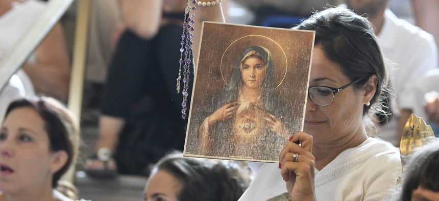 A woman holds a rosary and a picture of the Virgin Mary during a 2019 hearing in Albany, N.Y., challenging the constitutionality of the state's repeal of the religious exemption to vaccination