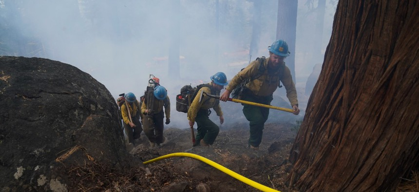 Members of a hotshot crew hike up the mountain while battling the Caldor Fire in South Lake Tahoe, Calif., Friday, Sept. 3, 2021.