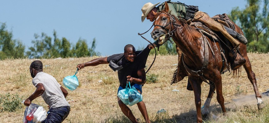 A Border Patrol agent on horseback tries to stop a Haitian migrant from entering an encampment on the banks of the Rio Grande near the Acuna Del Rio International Bridge in Del Rio, Texas, on Sept. 19.