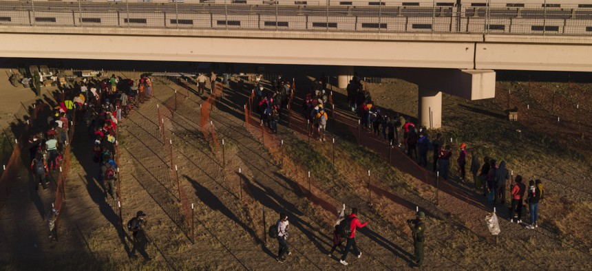 Migrants, many from Haiti, are seen in lines waiting to board busses at an encampment along the Del Rio International Bridge near the Rio Grande on Thursday.
