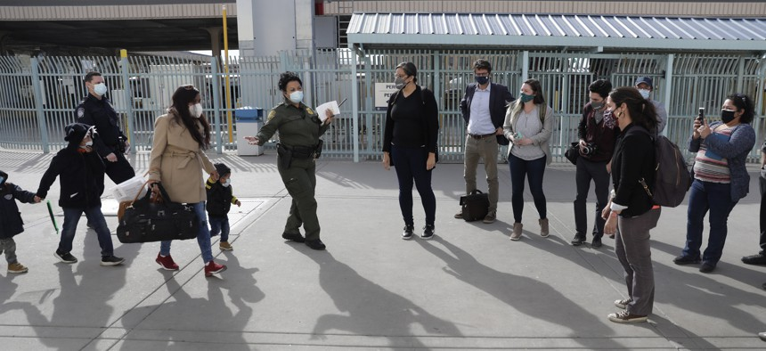 CBP officers and agents process a small group of asylum-seekers who have active applications under the Migrant Protection Protocols at the Paso del Norte Port of Entry in El Paso in February.
