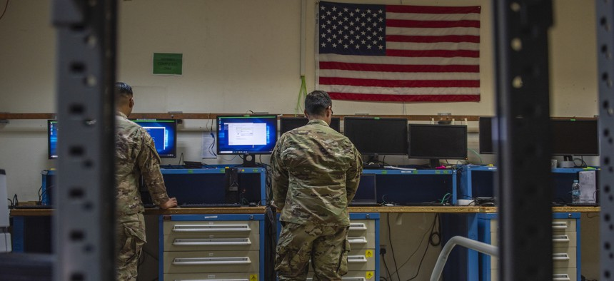Senior Airman Domenic Ferrante, 379th Expeditionary Communications Squadron executive communications technician, re-images a government laptop at Al Udeid Air Base, Qatar, Sept. 28.
