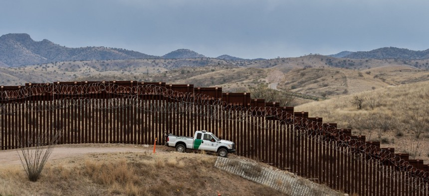 A Border Patrol officer sits inside his car as he guards the U.S.-Mexico border fence in Nogales, Arizona, in 2019.