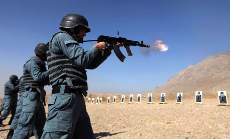 Afghan police recruits practice shooting at a firing range.