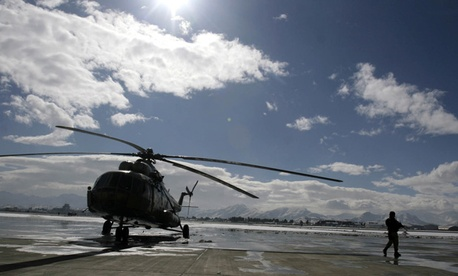 An Afghan Air Force officer walks away from a helicopter.