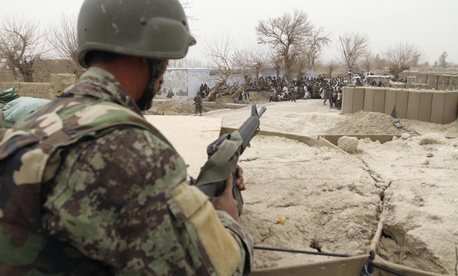 An Afghan soldier keeps watch in a guard tower at a military base in Kandahar.