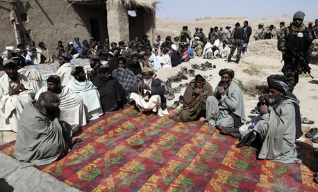 Afghan villagers pray during a ceremony Sunday for the civilians shot by a U.S. soldier in Kandahar.