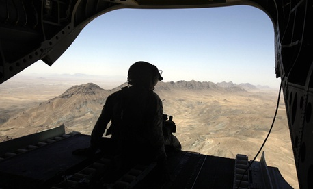 A U.S. helicopter tail gunner looks out over mountains in Afghanistan.