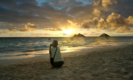 A tourist watches the sunrise near Hawaii's Lanikai Beach.