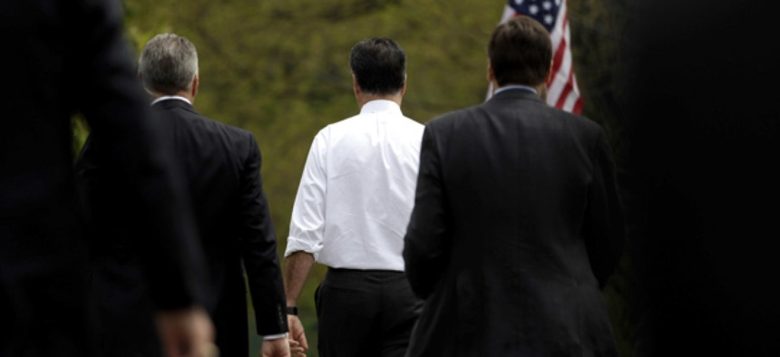 Mitt Romney walks with Secret Service agents.