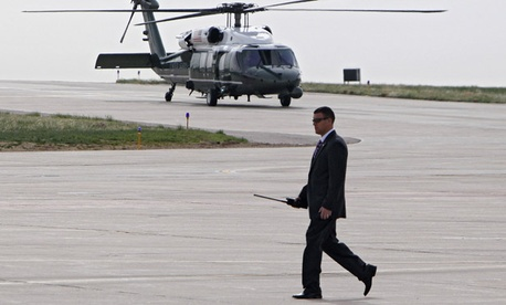 A Secret Service Agents walks the tarmac as Marine One carrying President Barack Obama taxis.
