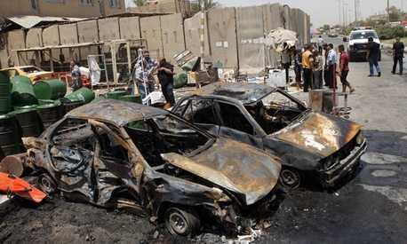 Iraqis inspect the aftermath of a car bomb attack in Baghdad's Shiite enclave of Sadr City Monday.