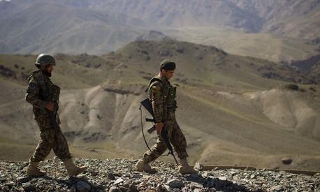 Two Afghan soldiers walk toward their outpost in Logar province in May.