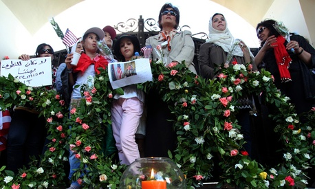 Libyans and Americans gather in front of the U.S. consulate gate to pay their respect to the victims of the attack on the U.S. consulate, in Benghazi, Libya.