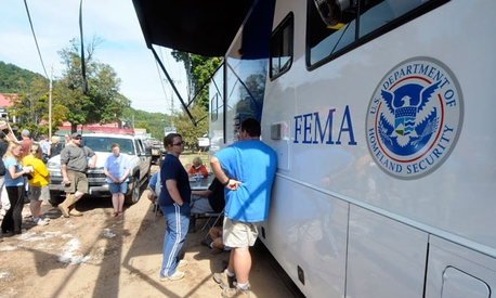 Flood victims line up to a FEMA trailer to get assistance in 2011.