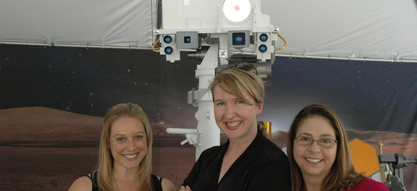 Curiosity Twitter team Courtney O'Connor, left, Stephanie L. Smith and Veronica McGregor pose with a model of Mars rover, Curiosity.