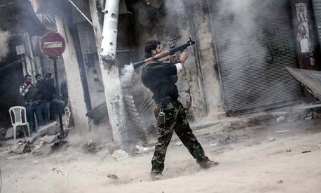 Nov. 04, 2012, a rebel fighter aims a missile toward a building where Syrian troops are hiding.