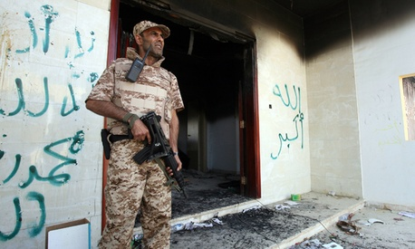 A Libyan military guard stands in front of one of the U.S. Consulate's burnt out buildings.