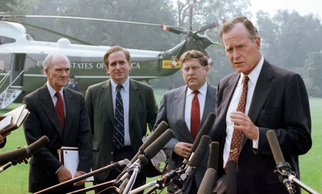 U.S. President George H. W. Bush talks with reporters on the White House lawn, Friday, Sept. 7, 1990 in Washington before flying to Andrews Air Force Base, Md. with his key aides to attend a budget negotiating session with congressional leaders
