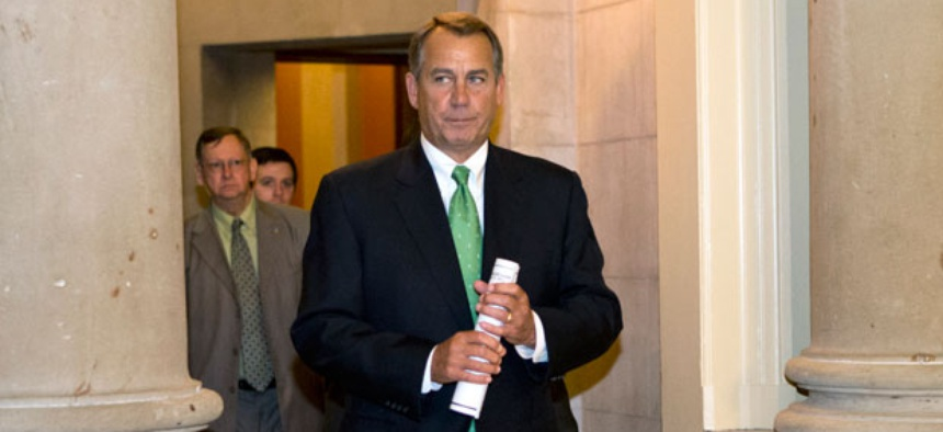 John Boehner walks to the House floor to deliver remarks about negotiations Tuesday.