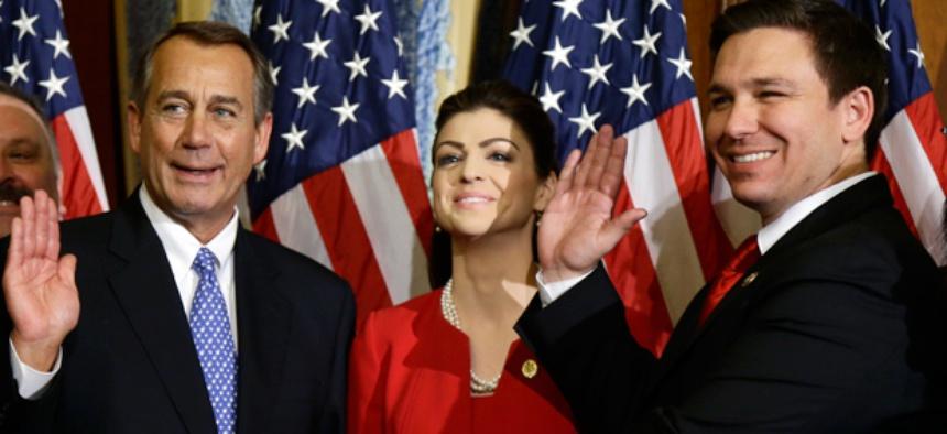 House Speaker John Boehner of Ohio performs a mock swearing in for Rep. Ron DeSantis, R-Fla.