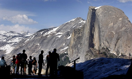 Visitors view Half Dome from Glacier Point at Yosemite National Park, Calif.