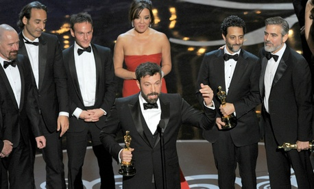 "Director/producer Ben Affleck, center, accepts the Academey Award for best picture for ""Argo."""