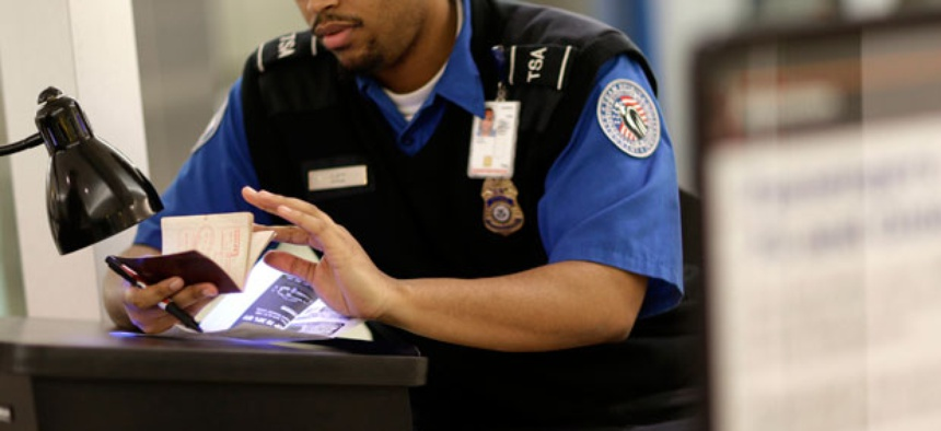 A TSA agent checks a passport at Baltimore Washington Airport.
