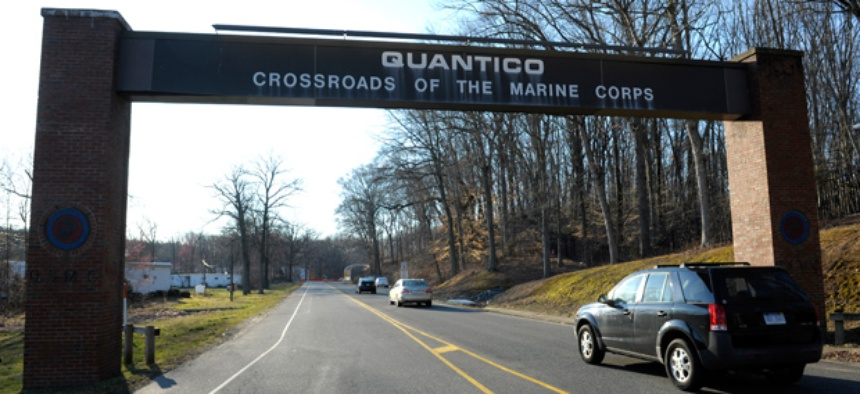 Cars pass under a sign at the entrance to the main gate at Quantico Marine Corps Base in Quantico, Va.