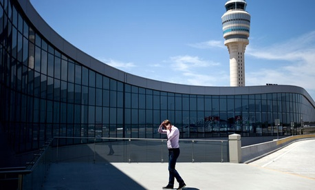 The control tower stands in the background as a passenger paces while on the phone outside the international terminal at Hartsfield-Jackson airport.