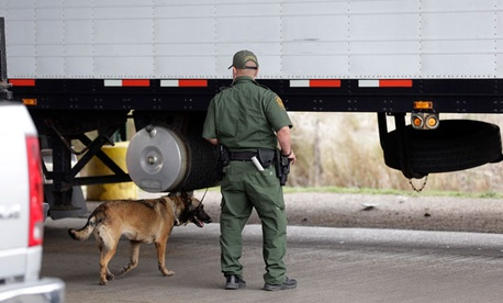 A Customs and Border Patrol agent and a security dog keep watch at a checkpoint in Falfurrias, Texas.