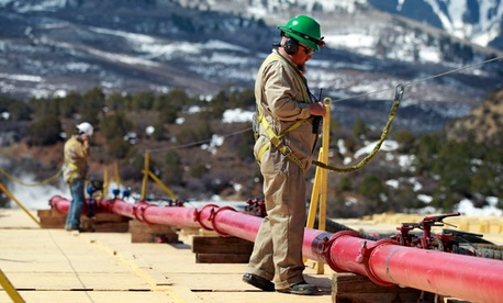 A worker helps monitor water pumping pressure and temperature, at the site of a natural gas hydraulic fracturing and extraction operation in western Colorado.